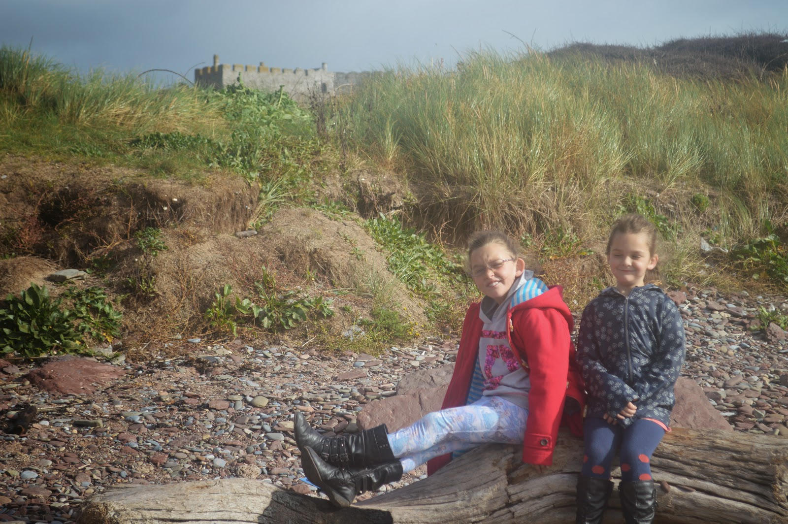 Girls sitting on log Manorbier Beach Pembrokeshire Wales