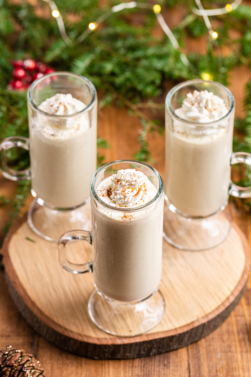 Over head photo of three glass mugs of Keto Eggnog (Dairy-Free & Sugar-Free) on a wooden round cutting board with Christmas lights in the background.