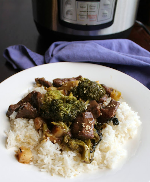 close plate of backstrap and broccoli served on rice with instant pot in background