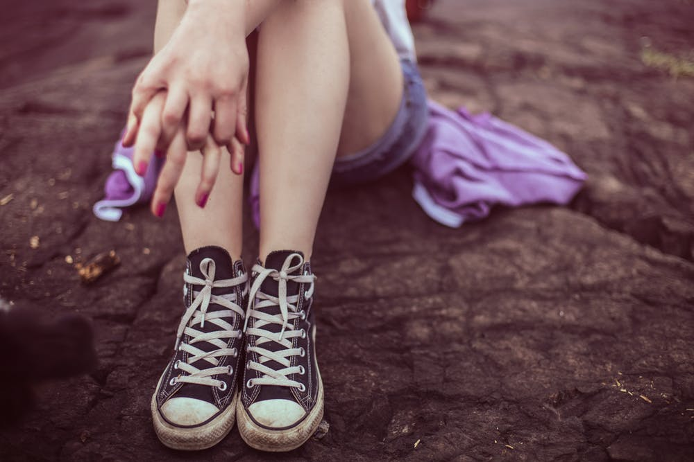teenage girl sitting on the ground wearing converse shoes
