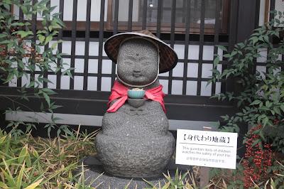 figura budista que representa un niño con pañuelo rojo