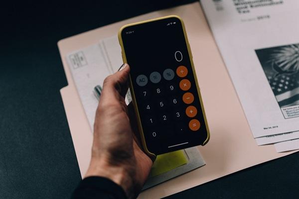 Mãos feminina segurando celular com calculadora aberta