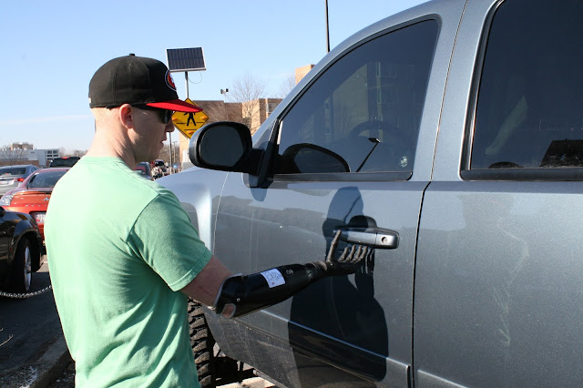 A man with a prosthetic arm reaches to open a car door.
