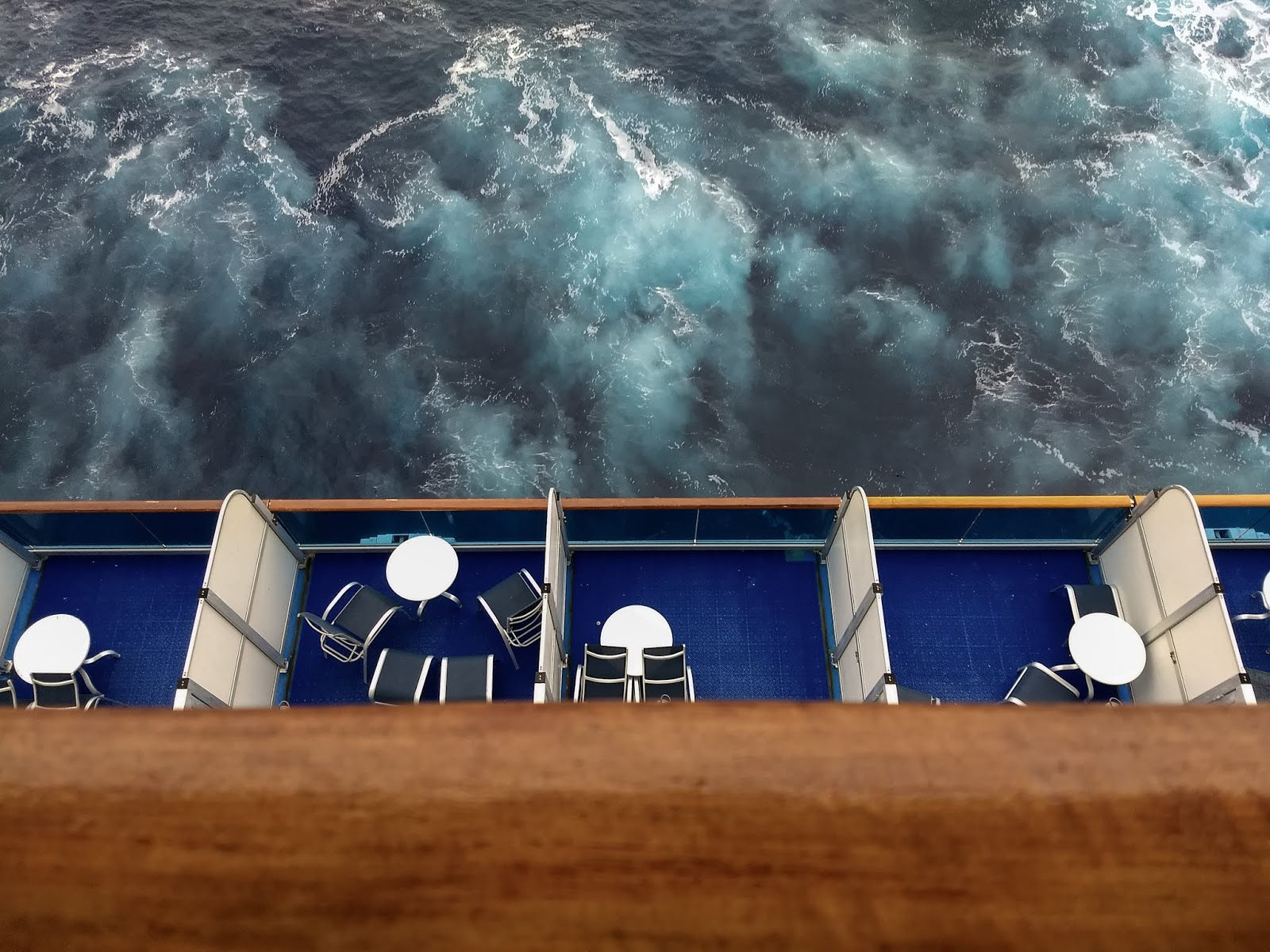 An aerial view of balconies on a cruise ship and agitated sea water.