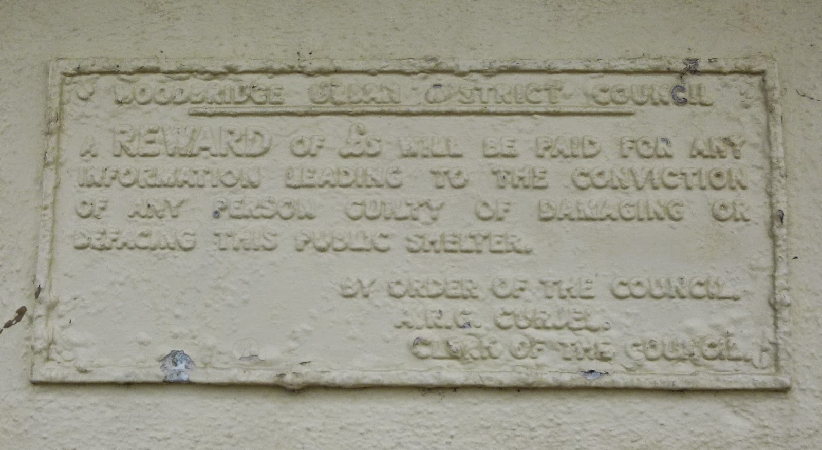 The old, painted over, plaque on the shelter in Woodbridge, Suffolk