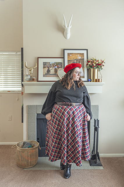 An outfit consisting of a red beret, black balloon sleeve sweater tucked into a red plaid skirt and black ankle boots.