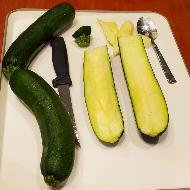 zucchini on a cutting board hollwed out with a knife and spoon