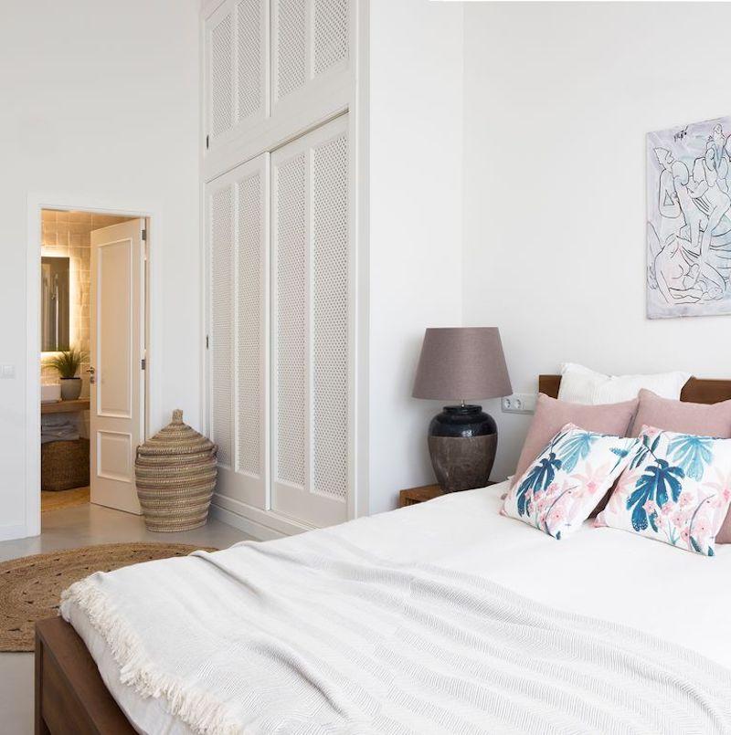 Dormitorio con gran armari empotrado con puertas de celosía pintadas de blanco