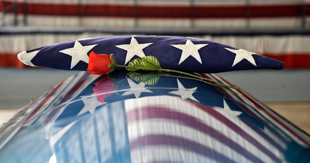 A coffin with a rose and folded American flag on top of it.