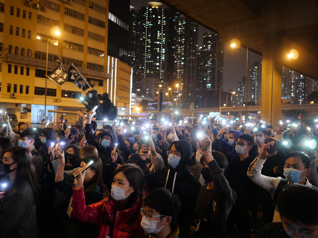 people holding their mobile phones with lights at a protest in Lai Chi Kok, Hong Kong