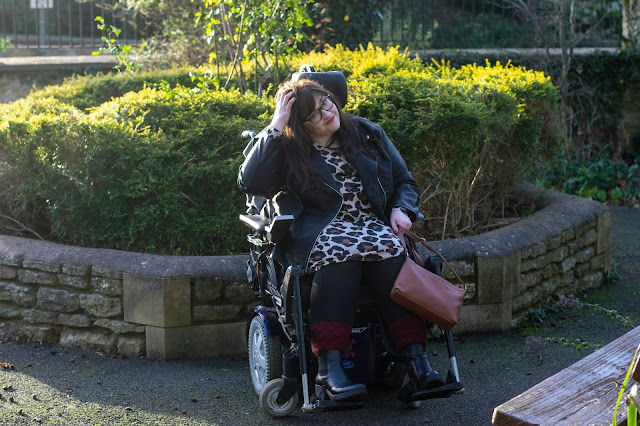 Plus size woman sat in powerchair wearing leopard print dress holding brown Mia Tui bag