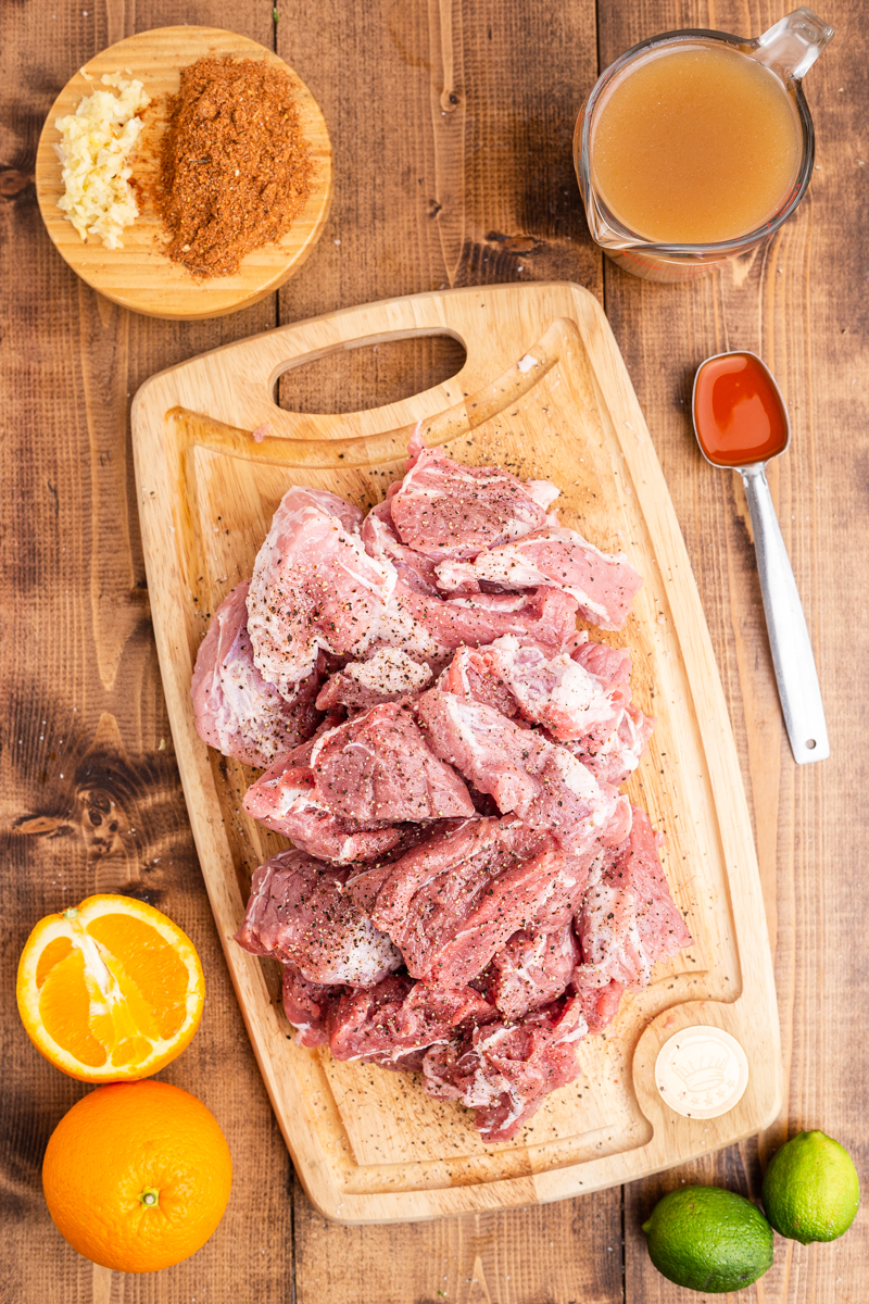 Overhead photo of the ingredients needed to make Easy Keto Pork Carnitas on a wooden table.