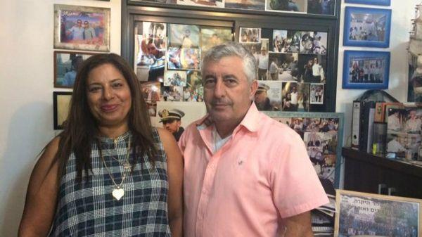 Irit y Asher Shahar frente al memorial a su hijo de Omri que han creado en su casa. (Renee Ghert-Zand / TOI)