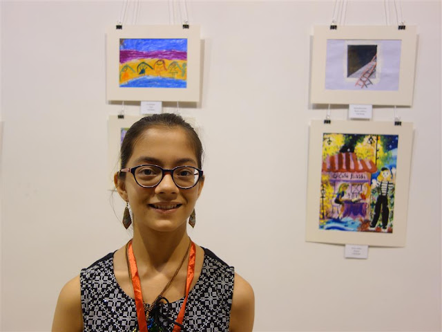Rucha Damle with her painting in the background at Khula Aasmaan exhibition (www.indiaart.com)