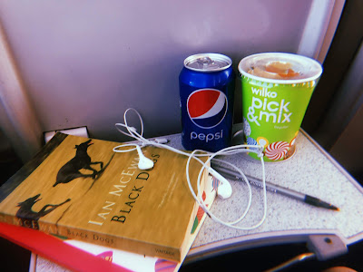 two books, a can of pepsi and some pick and mix on a train tray table