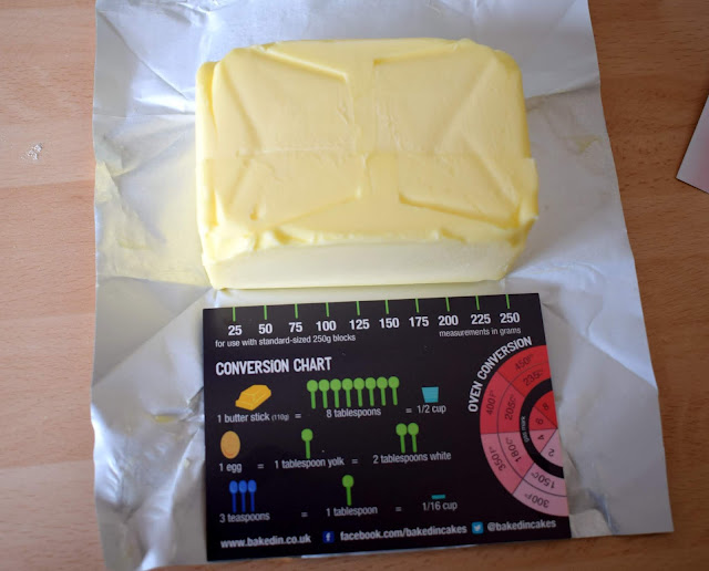 Large rectangle of baking butter showing a conversion chart card and butter measurer.