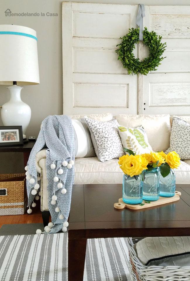 striped gray area rug, sofa, pom pom blanket, coffee table with blue mason jars holding yellow flowers