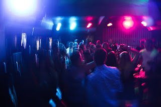 A blurry photograph of a nightclub or a party in nightclub style, with people dancing in an environment lit by coloured lights that do not illuminate the space as a whole.
