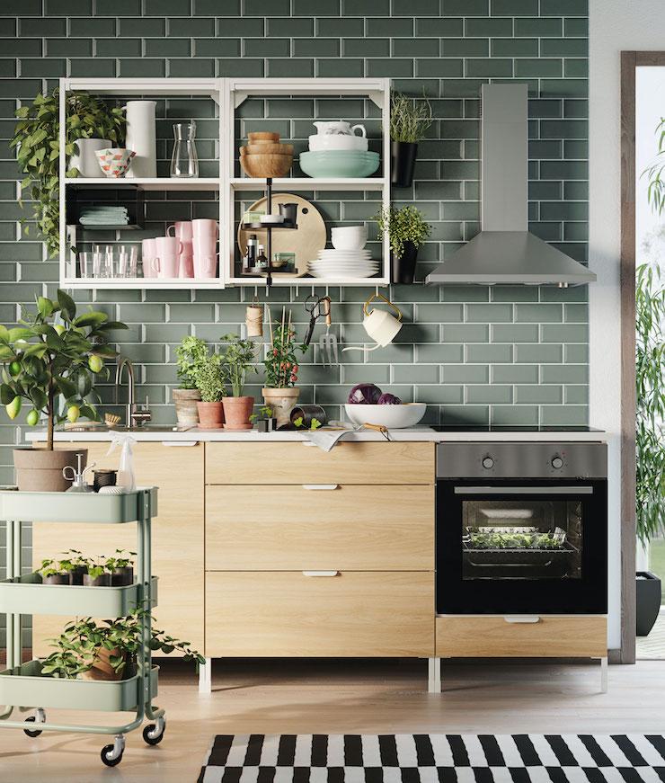 Cocina de IKEA con frente de madera y pared de ladrillo verde, del catálogo 2021.