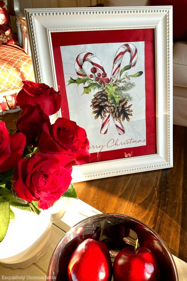 Framed gift bag on table with red roses and apples