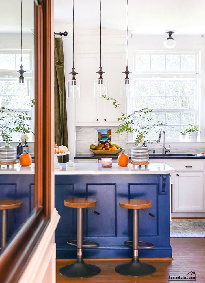 White and blue kitchen with orange and green accents