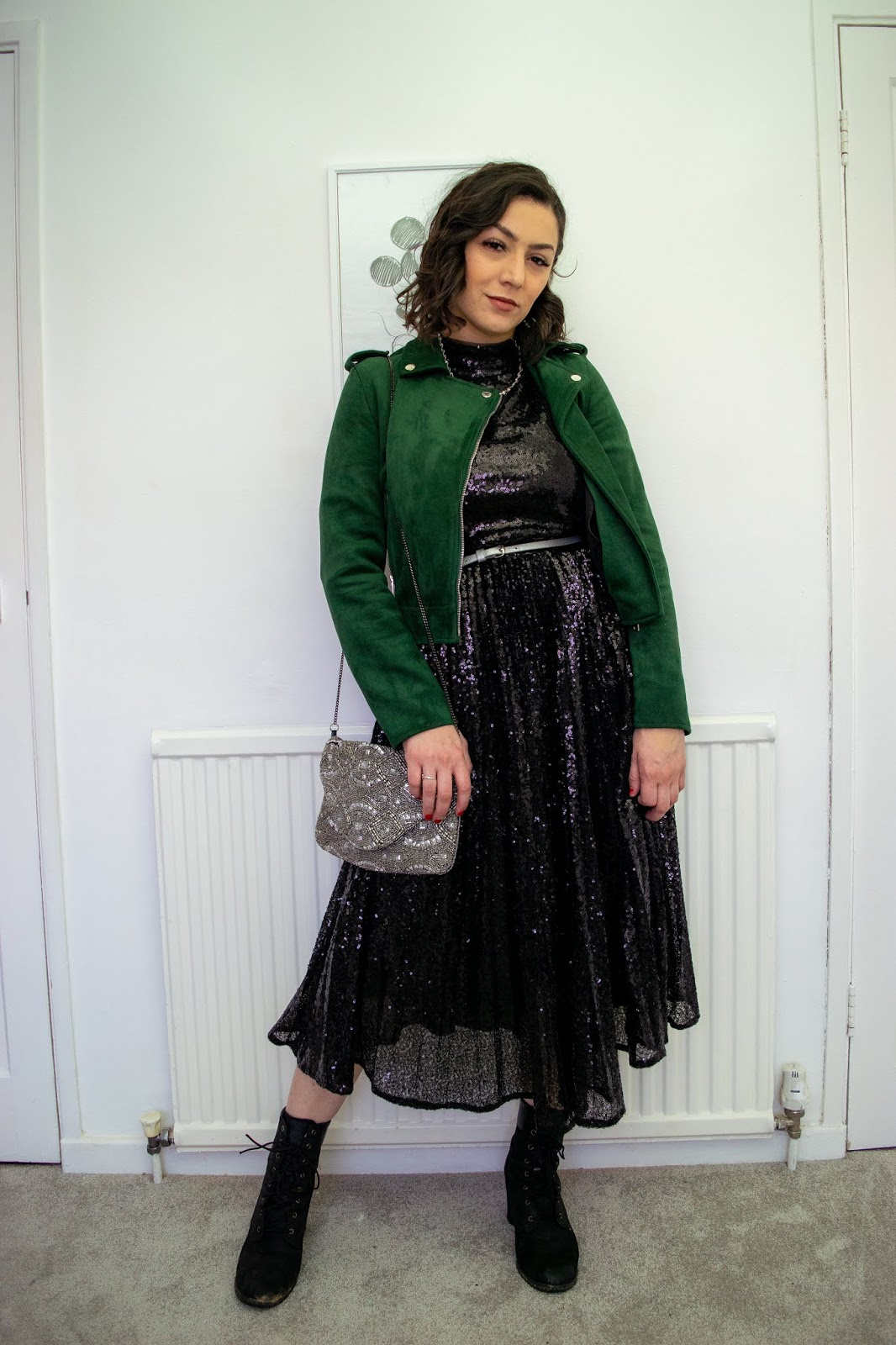 I'm standing feet shoulder width apart wearing a black sequin pleated dress with black Timberland heeled boots, a evergreen velvet biker jacket and a embellished silver clutch bag.