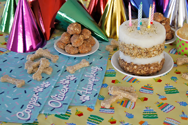 Dog birthday party buffet table with bandanas, hats, dog birthday cake, and homemade dog treats.