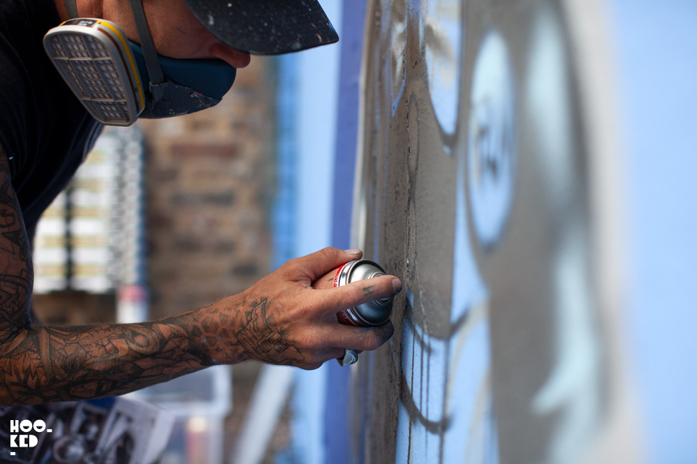 Artist Fanakapan at work spray painting his Hyper-realistic 'Up Yours'  helium balloon Mural