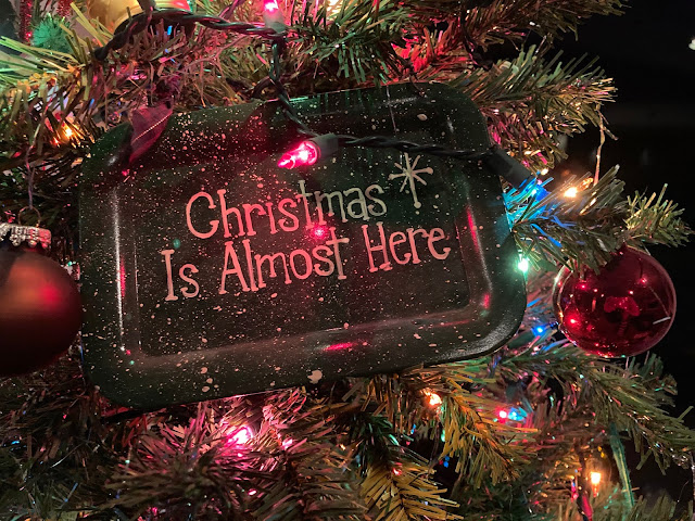Christmas Is Almost Here rectangular sign hanging on a tree along with red balls and lights.