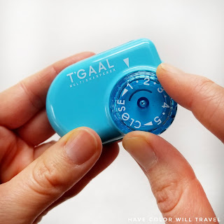 A close-up of a blue T'Gaal pencil sharpener focused on the dial of the sharpener. It is being held in the hand of a woman.