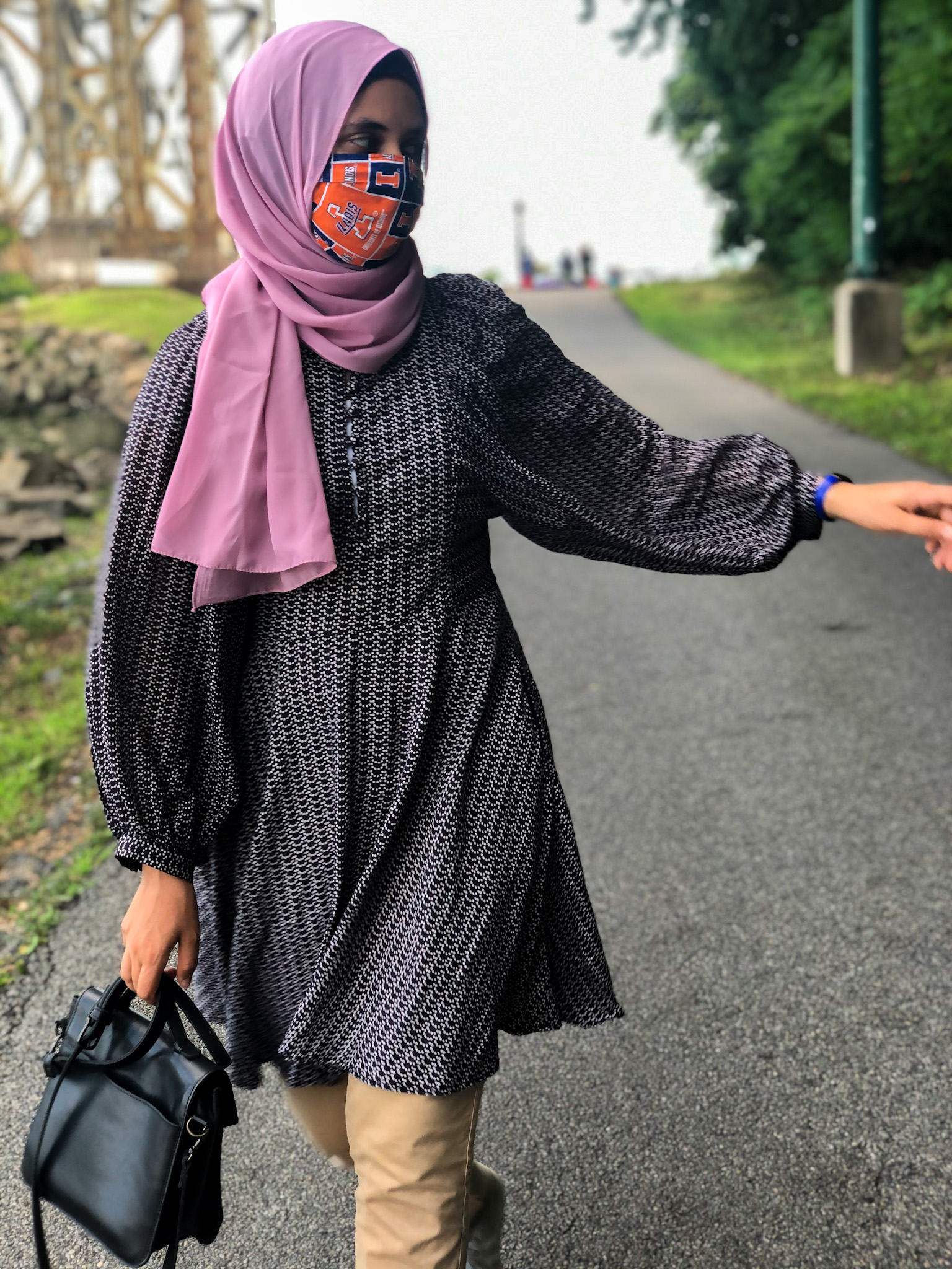 Sahara walking, black bag in right hand, pink scarf, pointing with left hand to the left