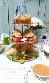 a 3 tiered afternoon tea stand with sandwiches, scones, and sweets, and a cup of tea in a vintage floral cup