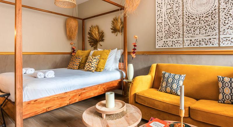 Salón con cama (con dosel de madera) de estilo chic