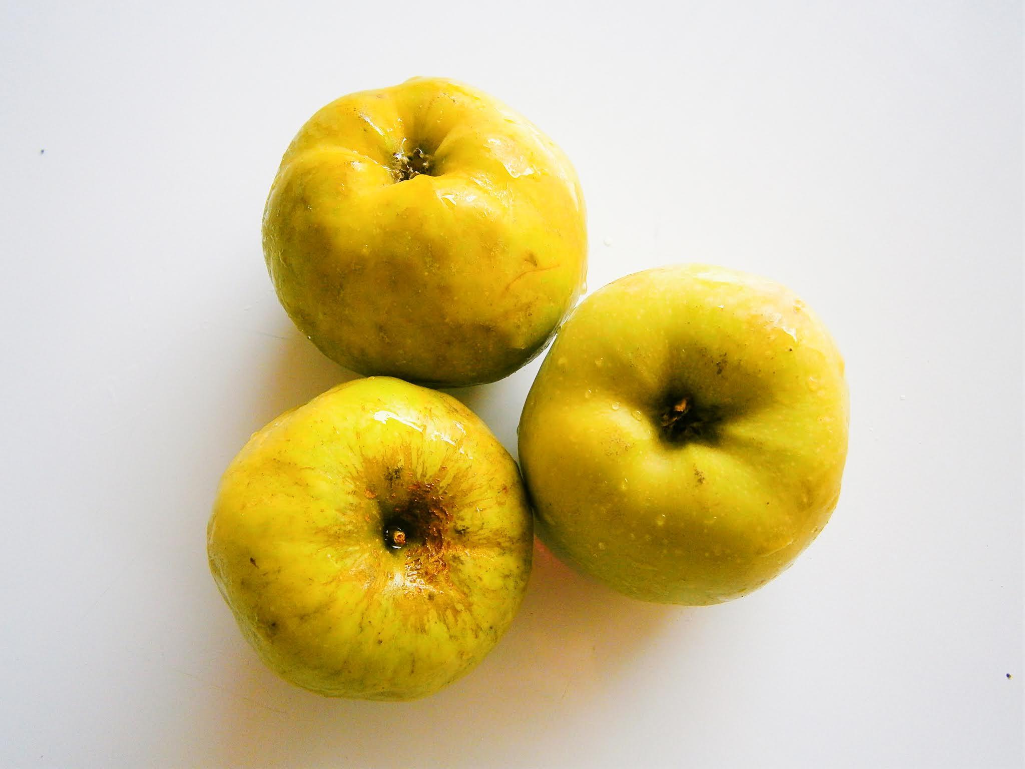 Manzanas verdes sostenidos de una mano y de fondo de color blanco