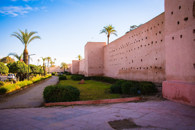 pink marrakech building with palm trees and sun