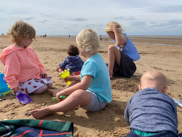 5 children of various ages digging on a sandy beach