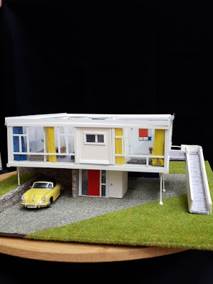 External view of a 1/48th scale model of a mid-century modern house. with a yellow car parked underneath, and a ramp up the right-hand side. The model is on a turntable, with a black cloth behind.