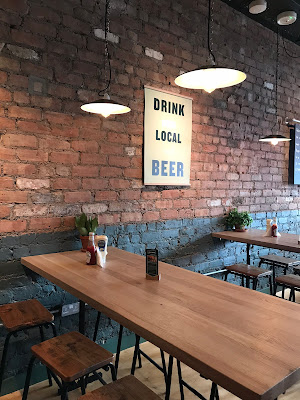 tables against a brick wall and a hanging sign that says drink local beer