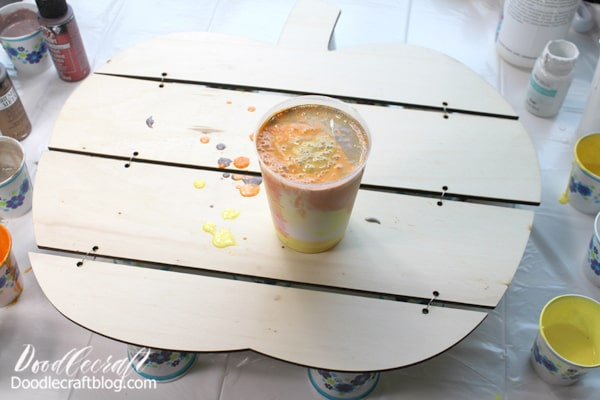 Then alternate colors of mixed paint and pour them in a larger mixing cup. Layer the colors in the cup like a bullseye.