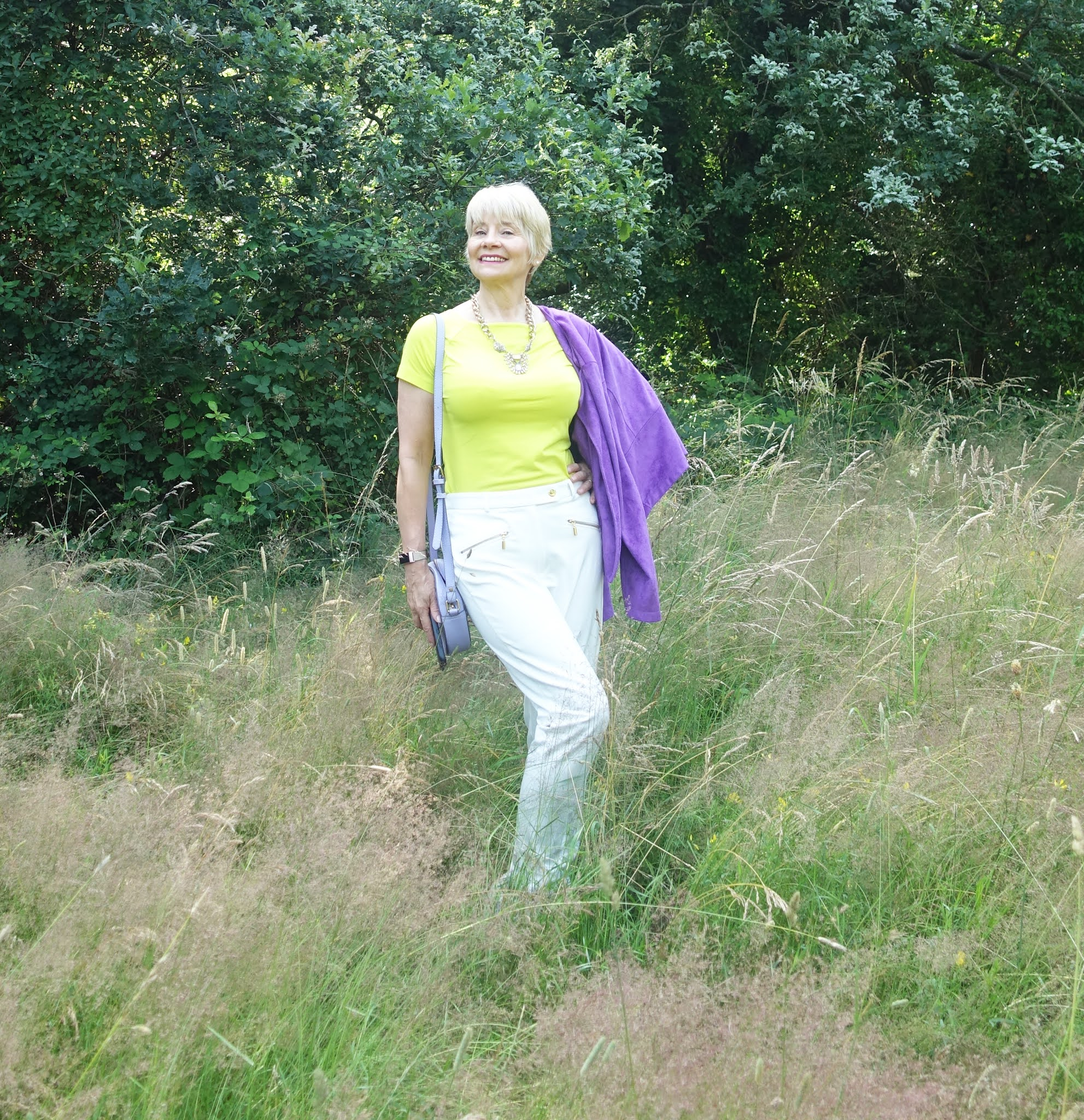 Posing in the grasses in Epping Forest, Is This Mutton blogger Gail Hanlon in the Style Not Age Challenge Jackets for July