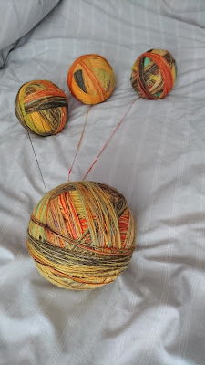 Three balls of handspun singles being wound into a ply ball