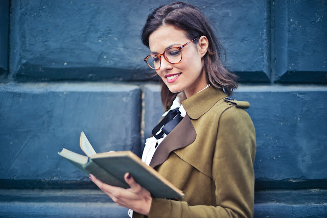 Woman reading a book wearing glasses
