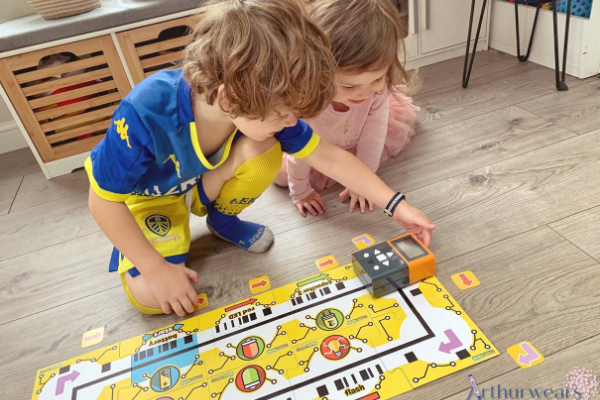 children playing with volty the coding robot and power tracks