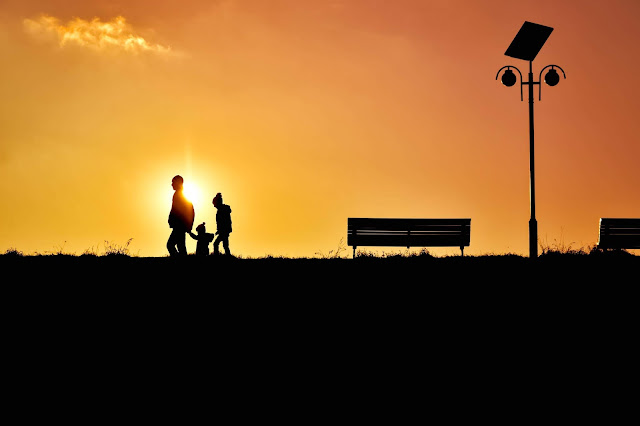 A family walking past a orange sunset in silhouette.