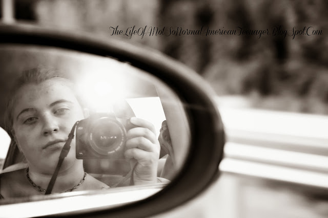 Young woman looking at herself in the car mirror with a camera - rosevinecottagegirls.com | Trisomy 13