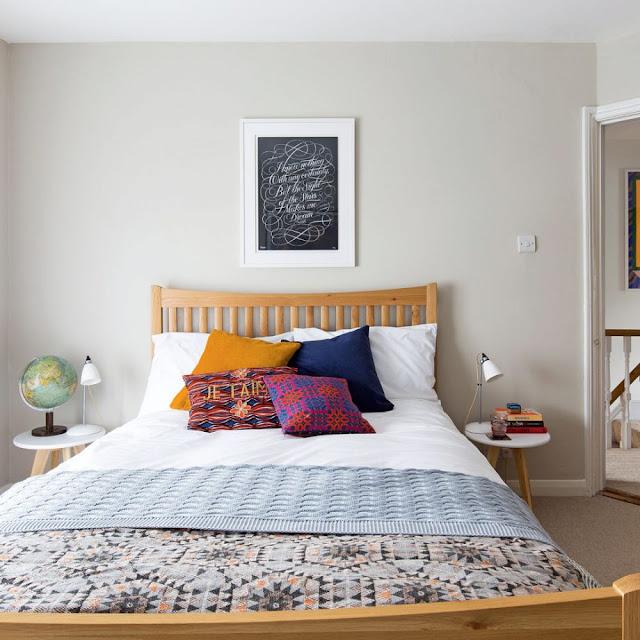 kamar tidur abu-abu kecil dengan tempat tidur ganda dan meja samping saja