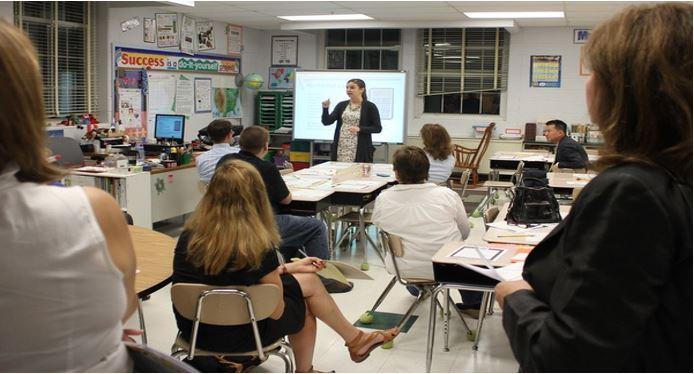 Luokkahuone, jossa aikuisia istumassa pulpeteissa ja kouluttaja luokan edessä.