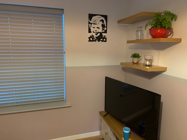 Corner of living room with print and shelves