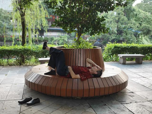 man sleeping on a circular bench at Liwan Park in Guangzhou