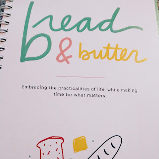 "pink and green words and a loaf and slice of bread grace the cover of the ""Bread & Butter"" kitchen planner"